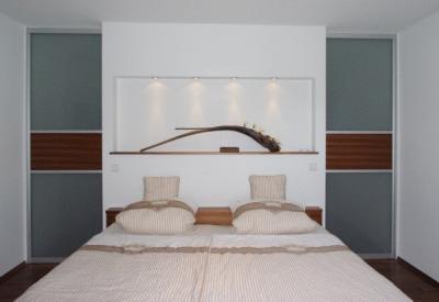 Begehbarer Kleiderschrank hinter dem Bett mit zwei seitlichen Gleittüren und als Eyecatcher: Wandelement mit beleuchteter Kunstnische